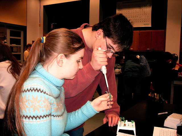 Two youths--a male and female-- concentrate in a lab procedure. The male holds a pipette. The female holds the sample.