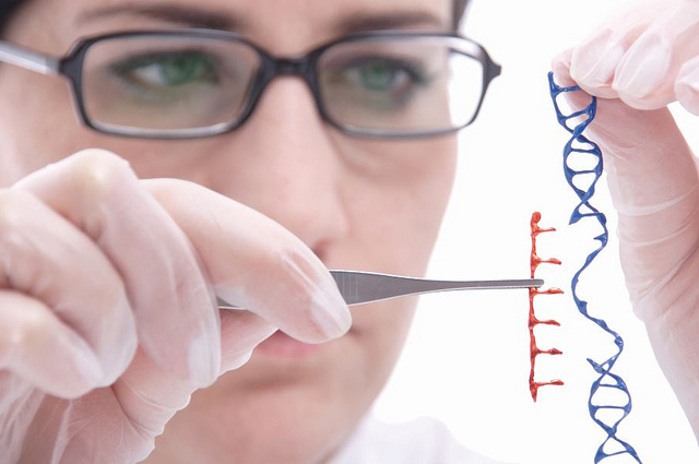 A scientist with eye glasses holds a DNA strand in their left hand at eye level. In their right hand they have an instrument containing missing DNA pieces.
