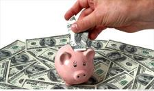 A piggy bank is surrounded by one hundred dollar bills. A hand is extended to place a bill into the piggy bank.