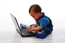 e5eeecd339a1 A young baby is fully dressed and sits in front of a laptop
