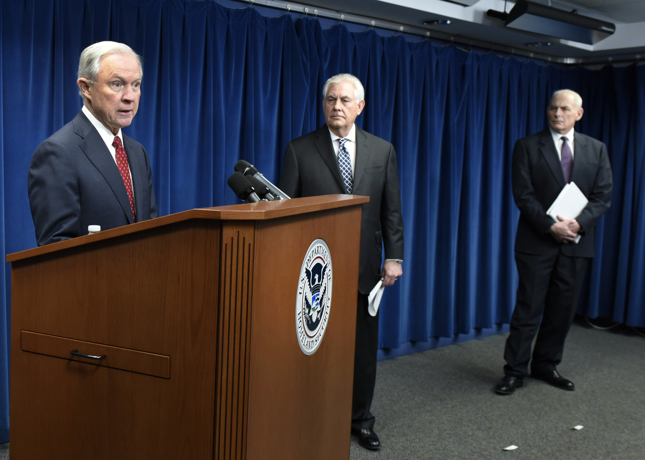 Attorney General Jeff Sessions stands behind podium at a press conference. Secretary of State Rex Tillerson and Secretary of Homeland Security John Kelly are looking towards him from the side.