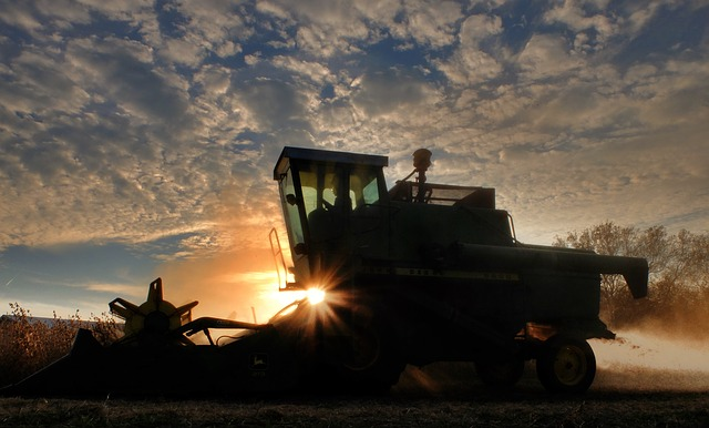 Silhouette of a tractor in a crop field. Against its background is a sunset, and blue skies with clouds