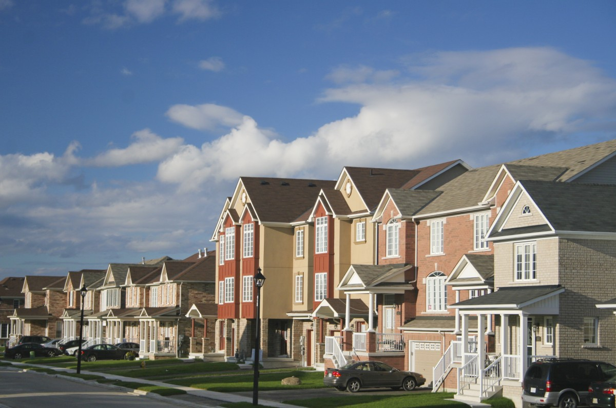 Suburban neighborhood on a sunny day with blue skies in the background.