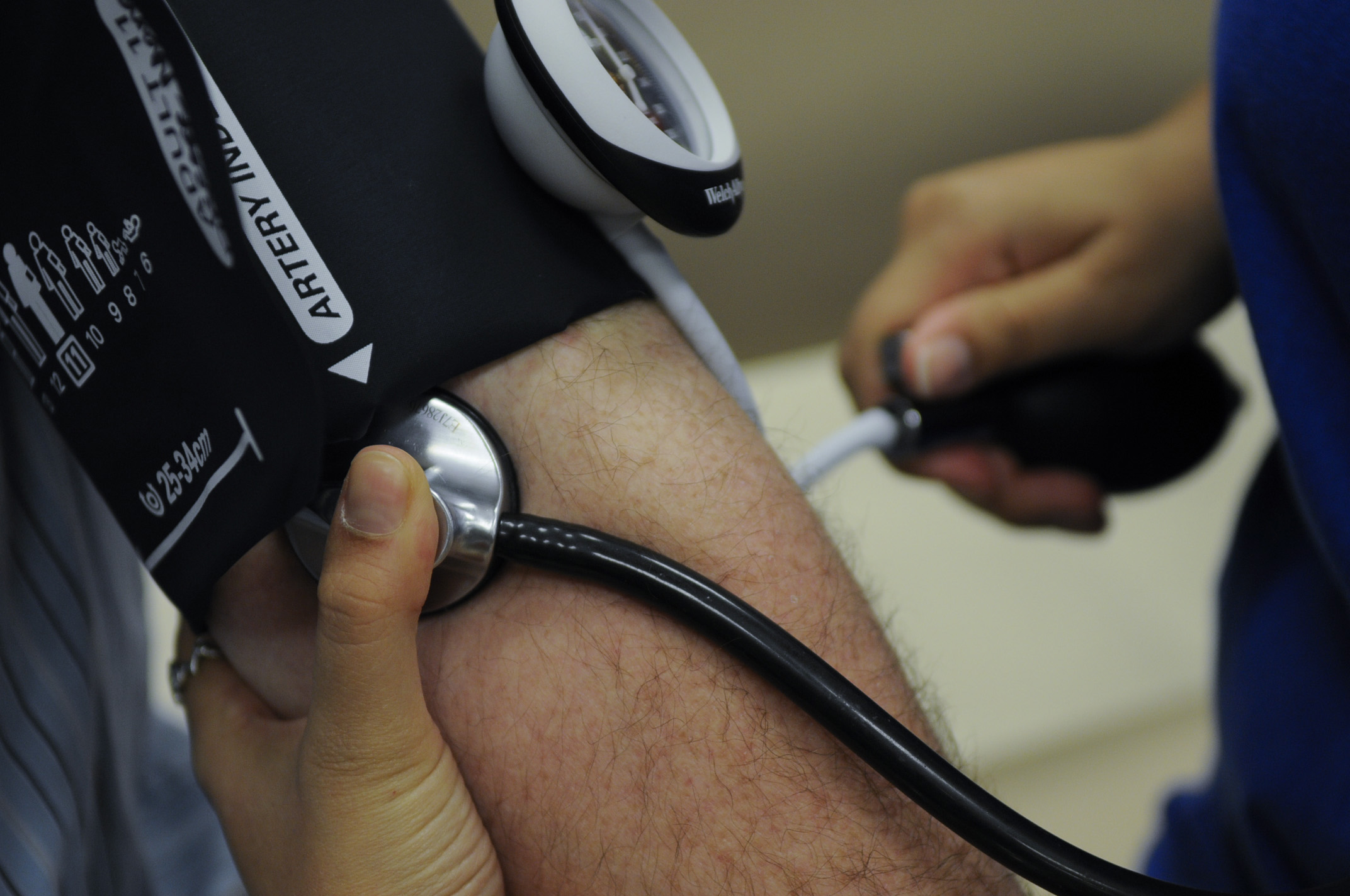 Blood pressure cuff around someone's arm and a stethoscope taking blood pressure