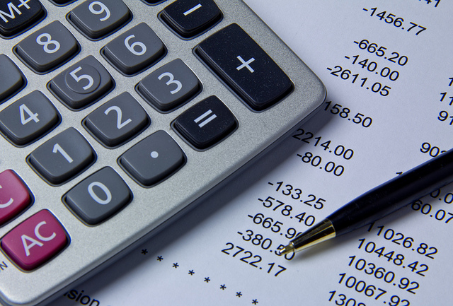 A calculator rests on top of an  sheet of paper with numbers that signify expenses. A pen rests nearby.