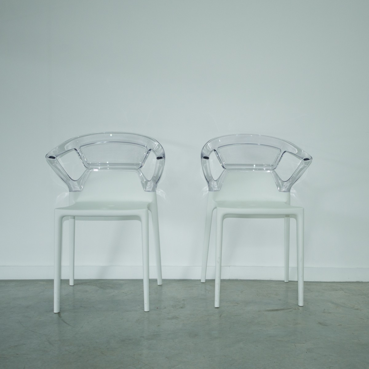 Two clear chairs sit side by side against a white wall.