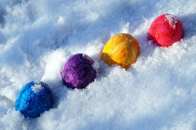 A row of brightly colored blue, purple, yellow and red eggs sits in the snow