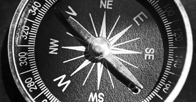 Gray-scale close-up of a compass. pointing north.