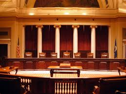 Large, empty wooden court room. 4 columns are across the wall behind the stand.