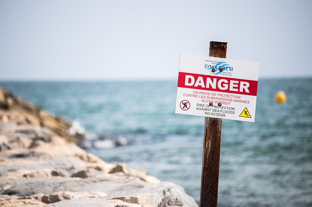 "Near a beach cliff, there is a warning sign that reads in bold letters ""Danger"""