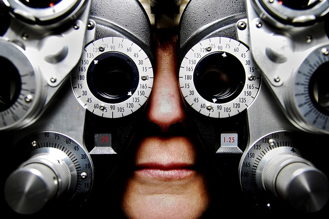 A patient looks through an eye doctor's instrument, which covers their face almost completely.