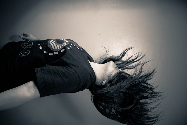 Gray scaled image, showing a woman who appears to be falling, with her hair covering her face and in motion.