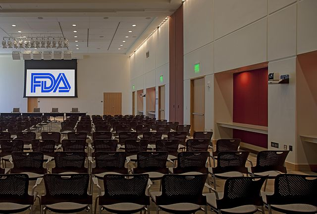 "An empty room with several rows of chairs facing a stage with a screen that reads ""FDA"""