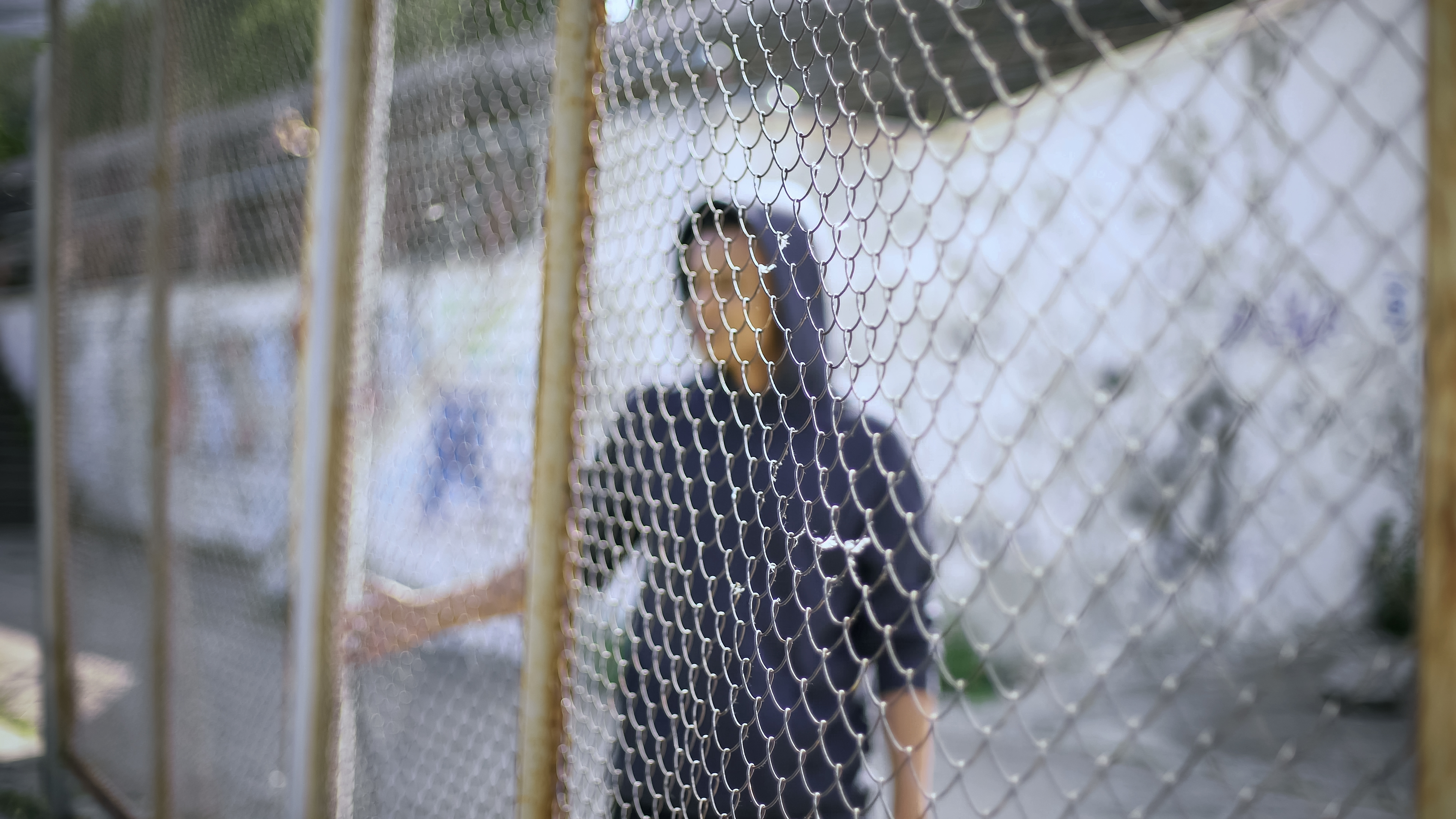 young man of color wearing a hoodie behind a cyclone fence