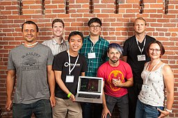A group of Biohackers. In the middle, one of the members holds an Apple laptop. Josiah Zayner  stands beside the laptop