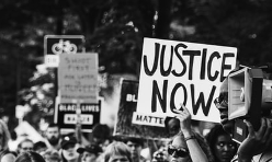 "A handwritten sign held overhead at a protest reads ""JUSTICE NOW"" in all caps"
