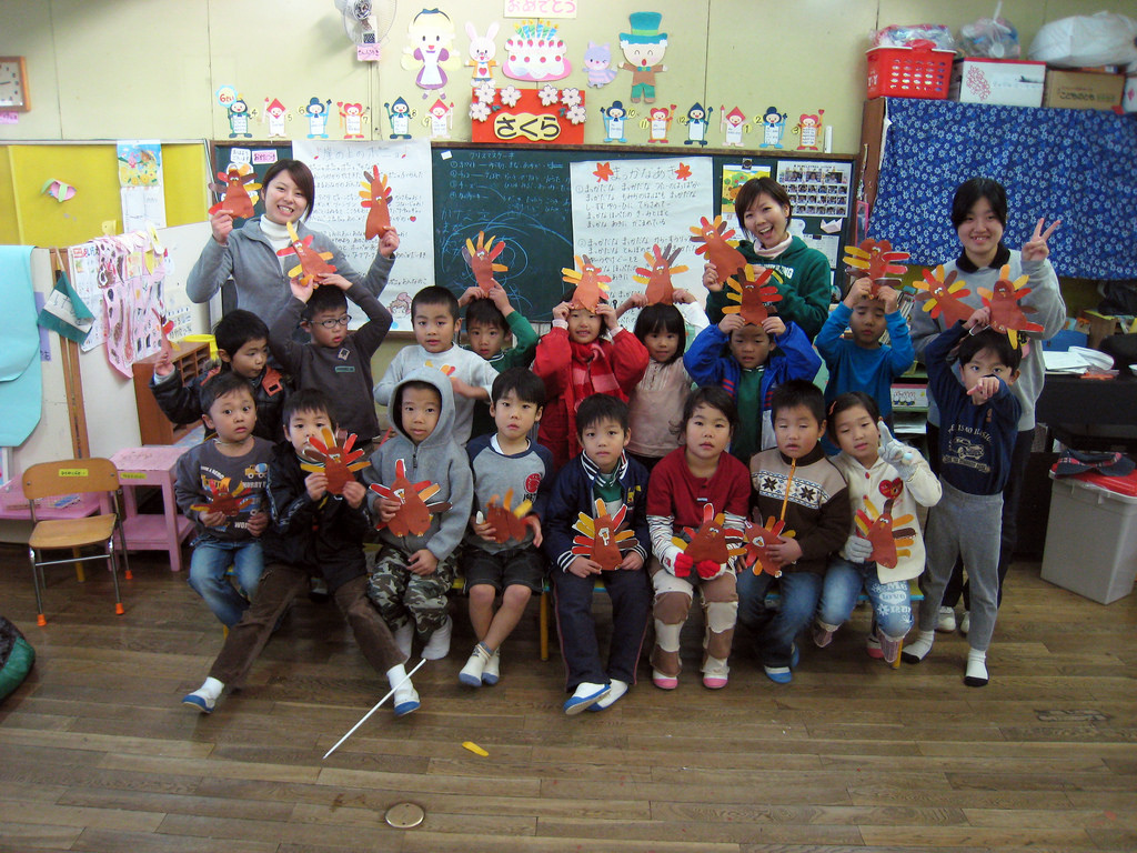 Class of kindergartners and three teachers holding up paper turkeys