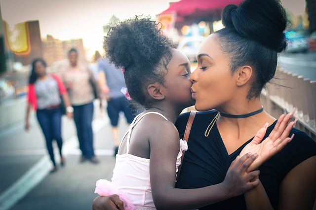 A black woman kisses a young black girl with joy and love expressed on their faces. In the background, there is a city back drop with other people walking on the sidewalk is featured, but out of focus and blurred.