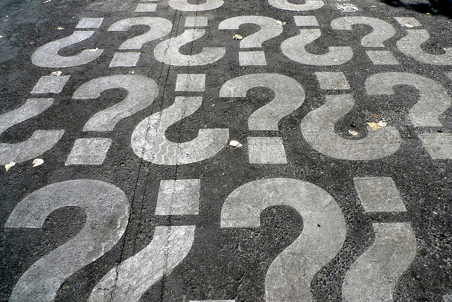 Repeated pattern of question marks, on asphalt surface.