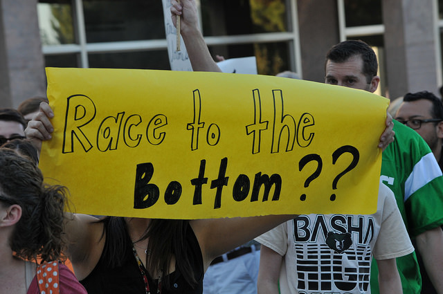 "Protesters hold a yellow sign that reads, ""race to the bottom??"""
