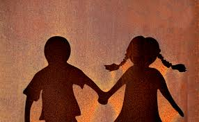 Burnt orange background with a shadow of two children holding hands. There is a boy on the left and a girl with pigtails on the right.