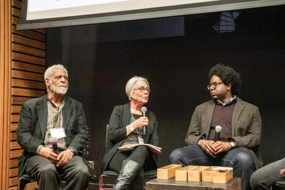Seated, from left to right: Panelists Troy Duster, Rosemarie Garland-Thomson, and Osagie Obasogie holding microphones. Garland-Thomson holds her microphone up as she speaks.