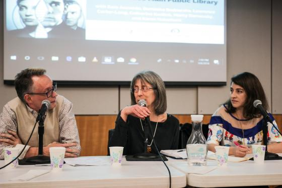 From left to write, Lawrence Carter-Long, Marcy Darnovsky, and Sara Acevedo sit at a table with microphones in front of them. Darnovsky looks at Carter-Long as she speaks, Acevedo looks toward them.