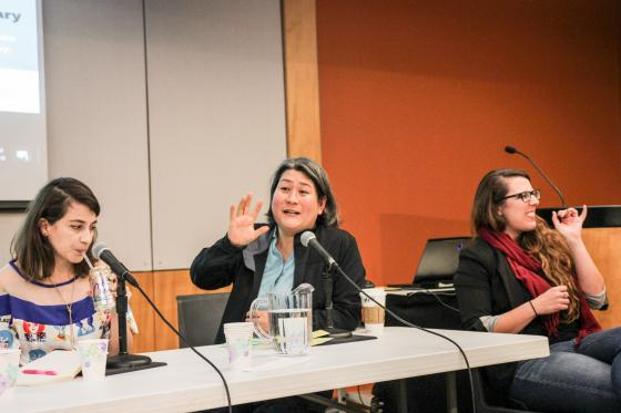 Karen Nakamura, seated behind a table, gestures as she speaks. On the left, Sara Acevedo sips a beverage. On the right, the ASL interpreter.