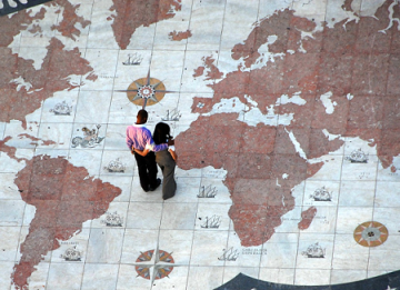 A heternormative couple looks down at the ground, which features a world map of 7 continents.
