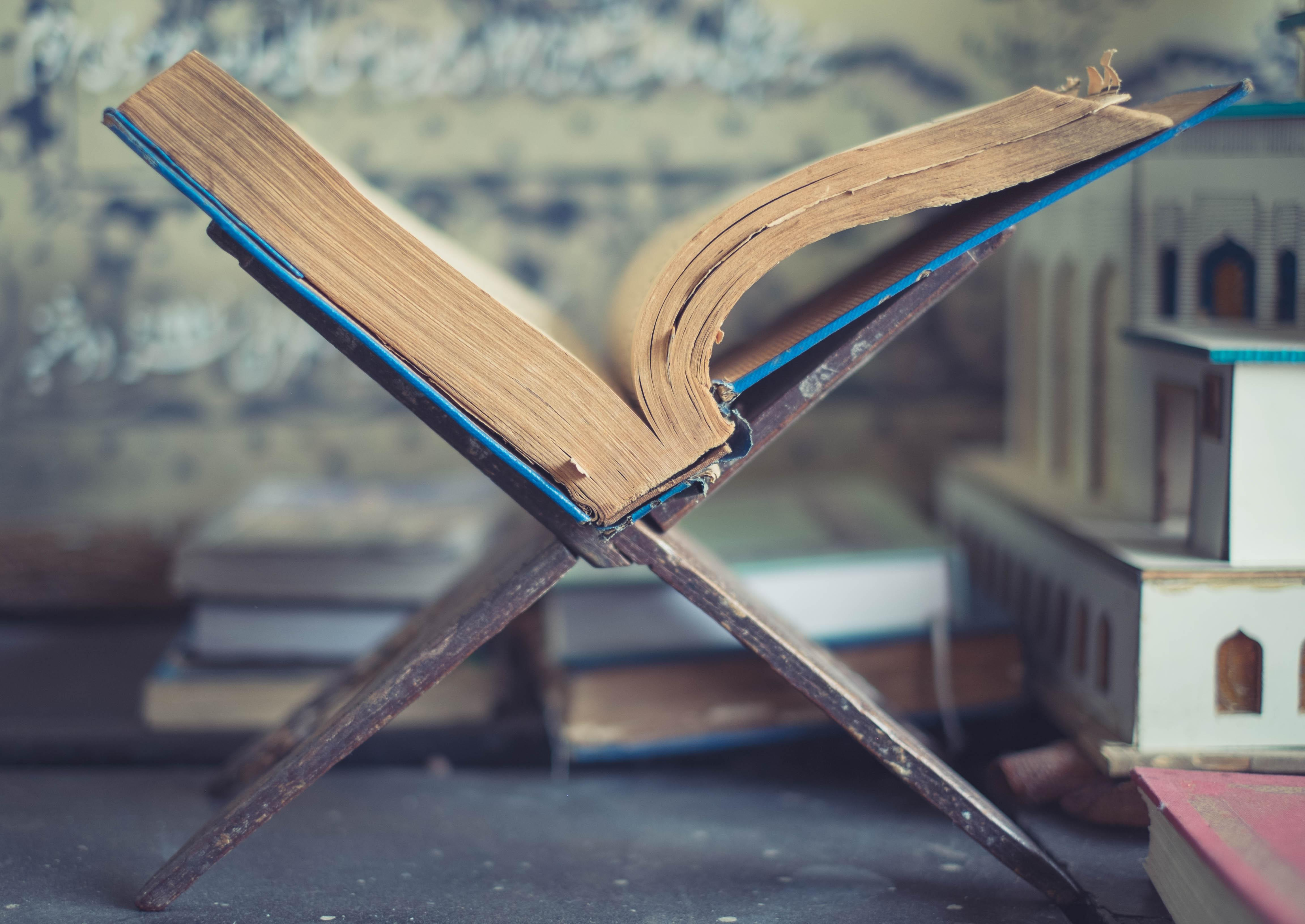 A book lies open in the middle, propped up by a book stand. Out of focus, in the background are several other books and religious artifacts.