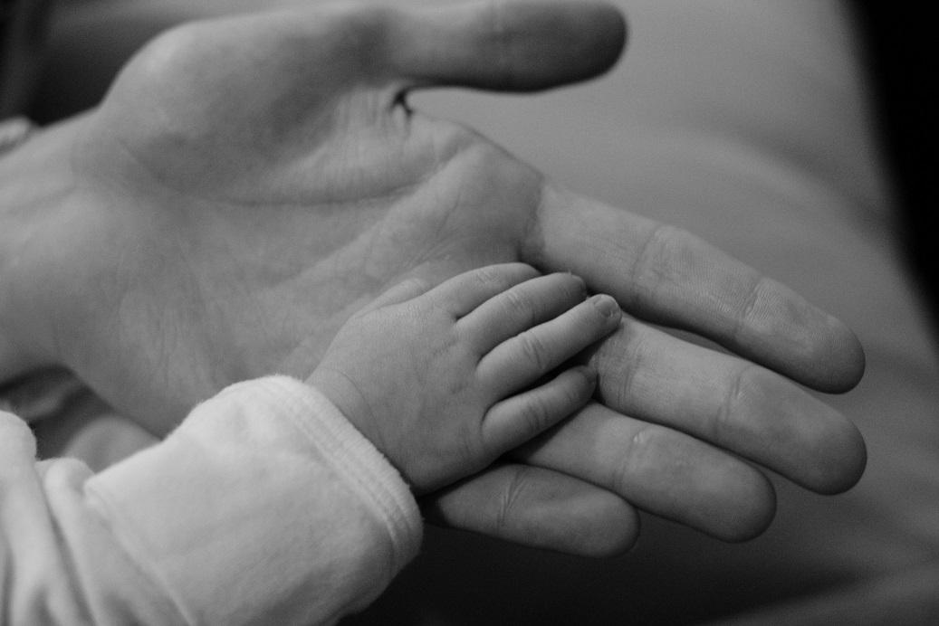 Black and white photo of a child's hand touching a parent's palm.