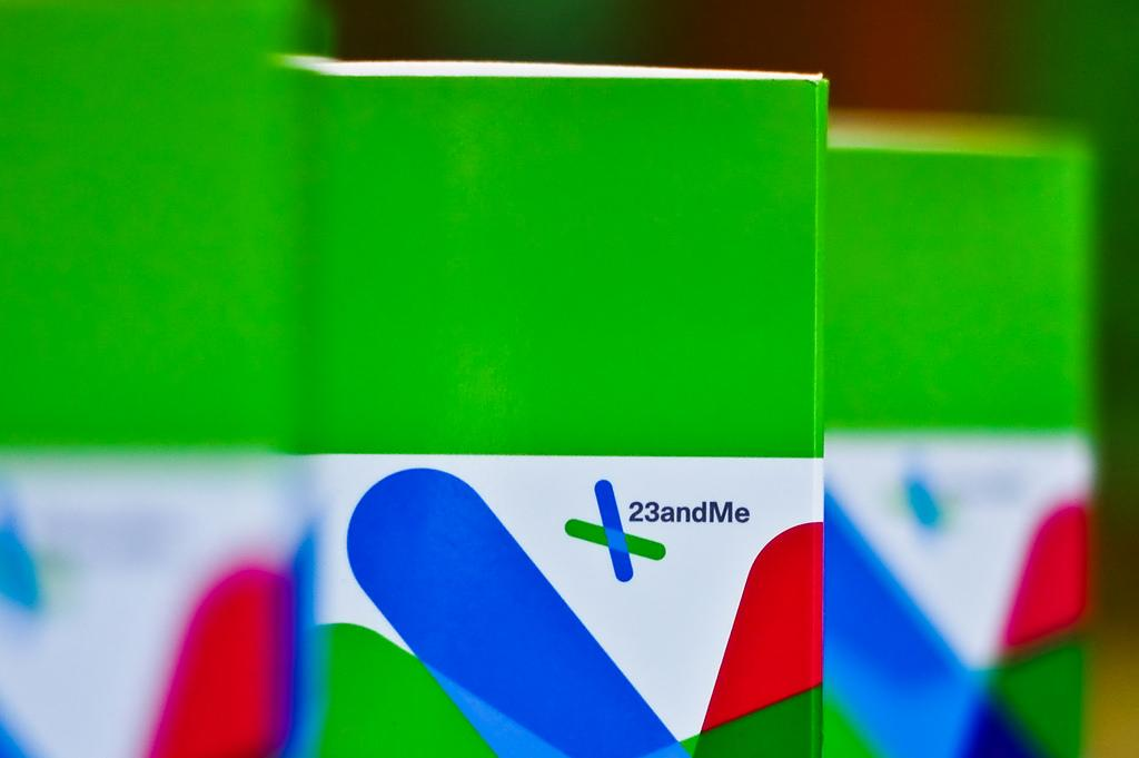 Three boxes of 23andMe kits stand upright in a line. Two of the boxes have been blurred, and one of them is centrally focused.