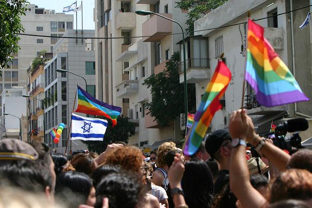 Image of goup of people waving pride flag and Israeli flag.