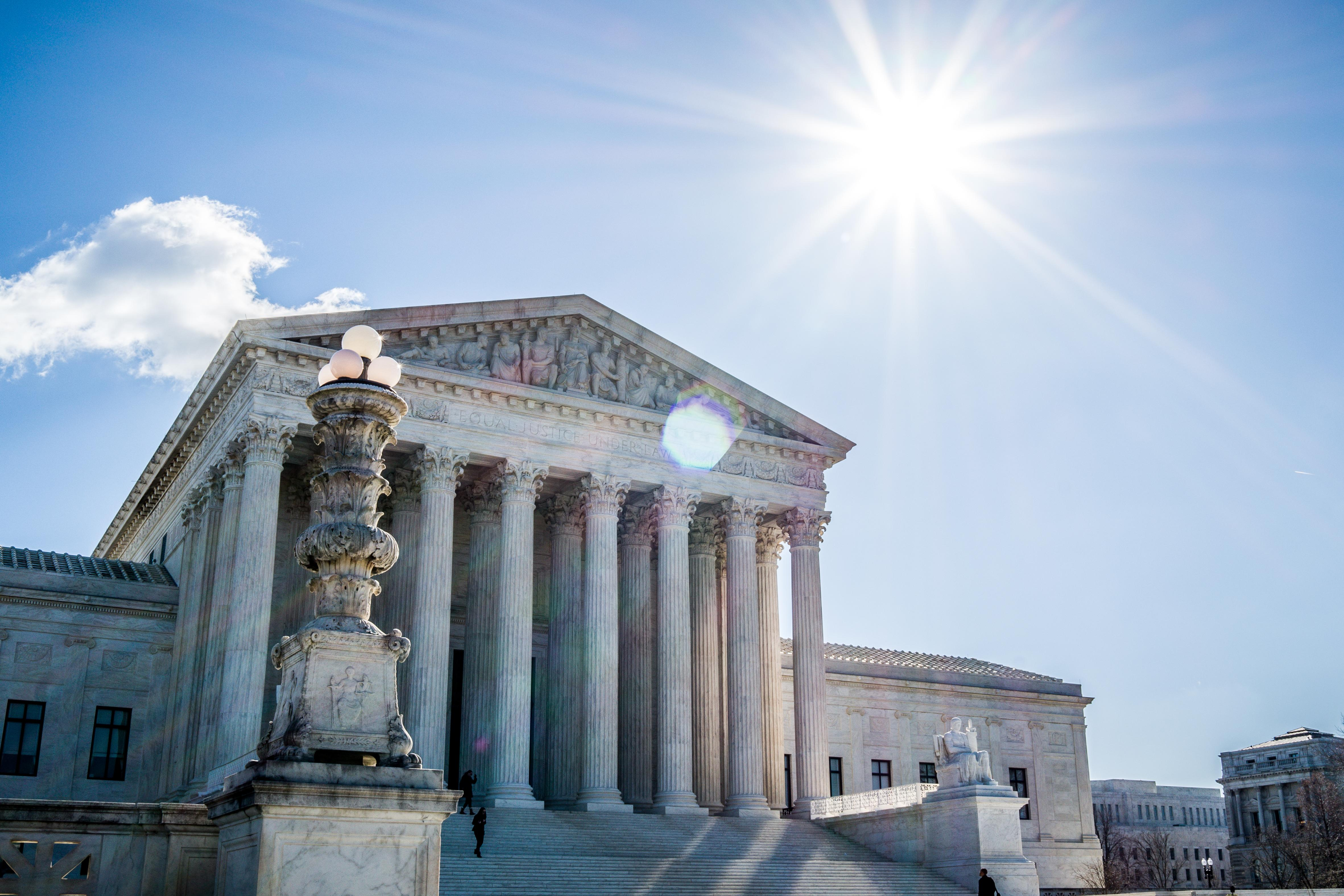Landscape photo of the US Supreme Court building. with the sun and blue sky above.