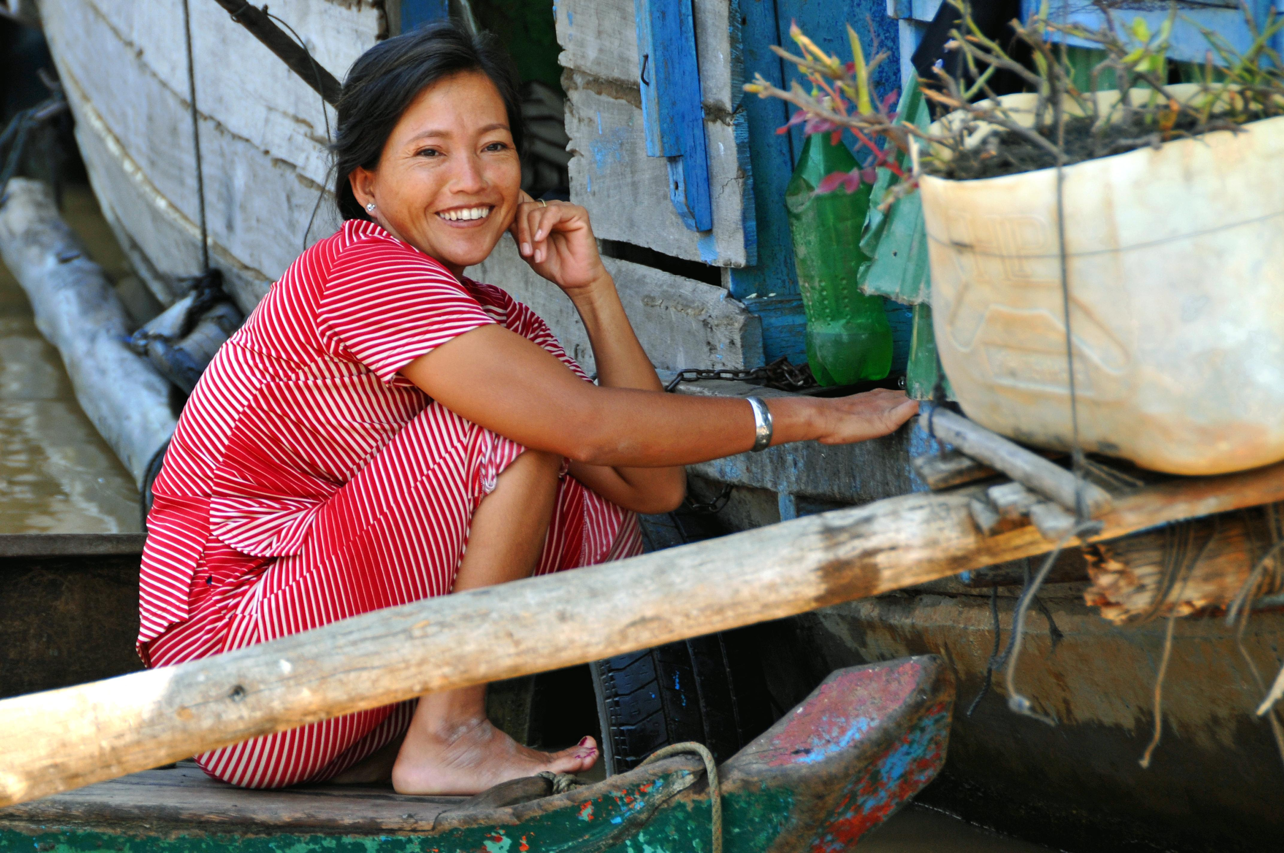 Portrait photo of a Cambodian woman smiling, while sitting on the ground.