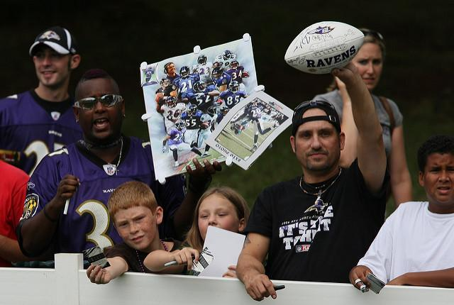 Excited Baltimore Ravens fans are standing behind a fence hoping to get their gear signed.