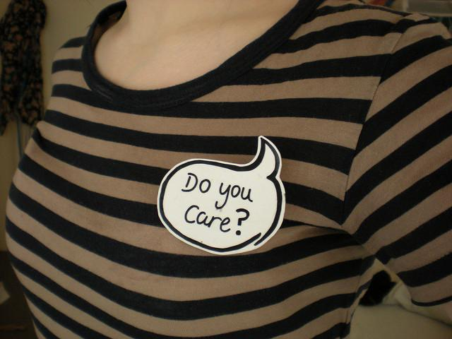"Against a shirt with black and gold stripes, a sticker reads ""Do you care?"" in a thought/speech bubble."