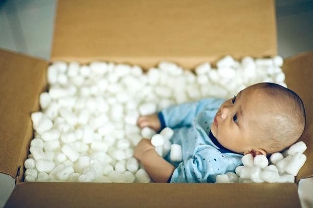 A baby stiffly lays in a cardboard box, surrounded by package bubble wrap.