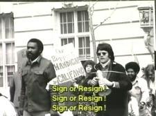 "Black and white screenshot of a scene in the documentary The Power of 504, which highlights a victory in disability justice (reflected in Section 504 of the 1973 Rehabilitation Act). Protesters advocate for the civil rights of people with disabilities. Some hold signs stating ""Our biggest handicap is [HEW Secretary Joseph] Califano!"" Caption reads ""Sign or resign!"""