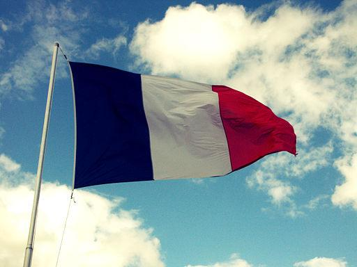 The French flag blows in the wind, against a blue sky with clouds.