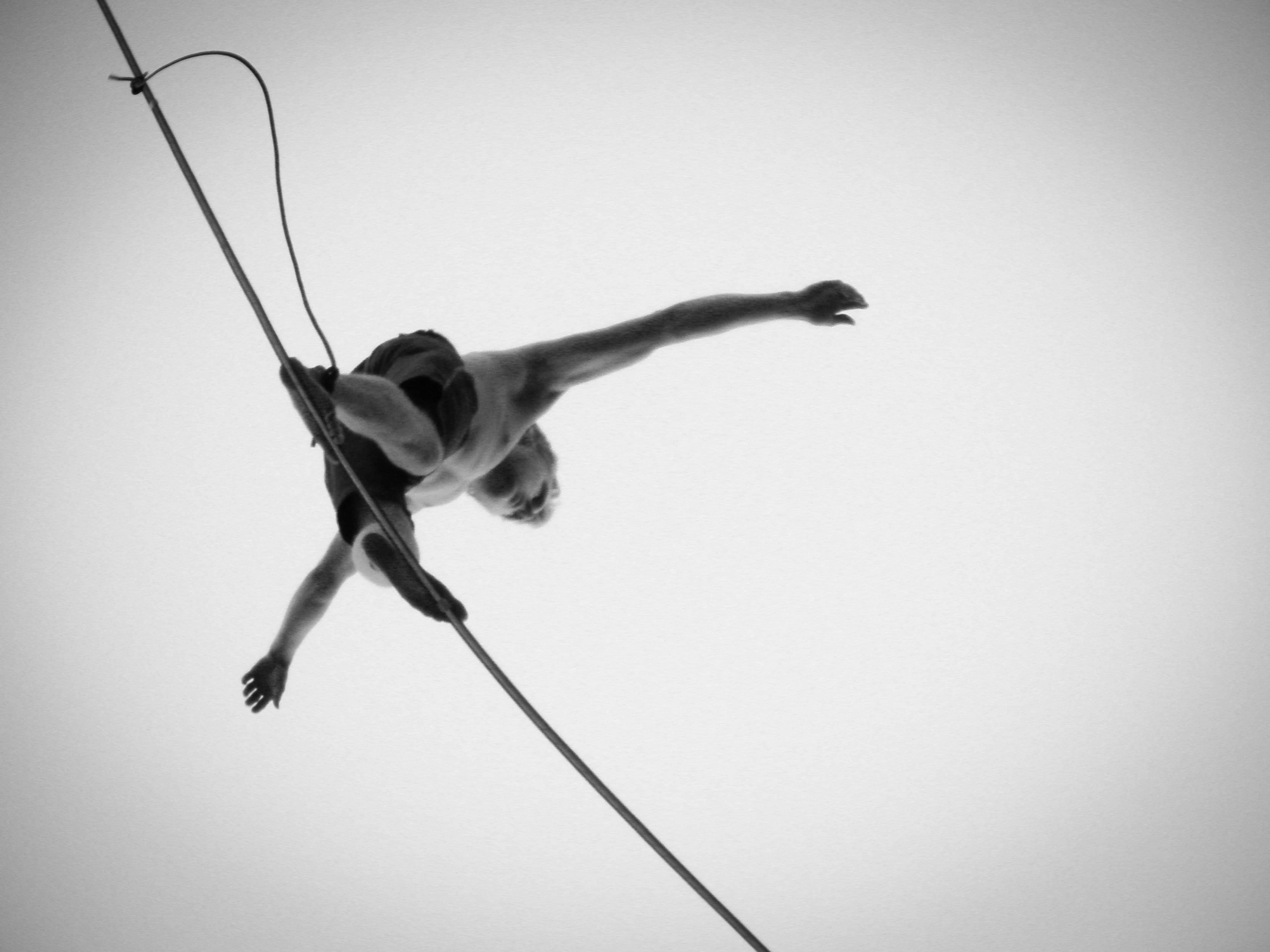 Black and white photo, in bug's eye view, looking up at a person balancing on a tightrope.