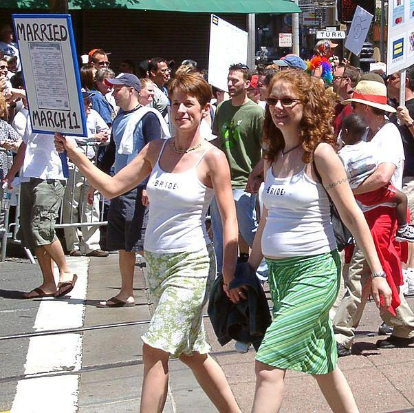 Lesbian couple holding hands and walking on the street