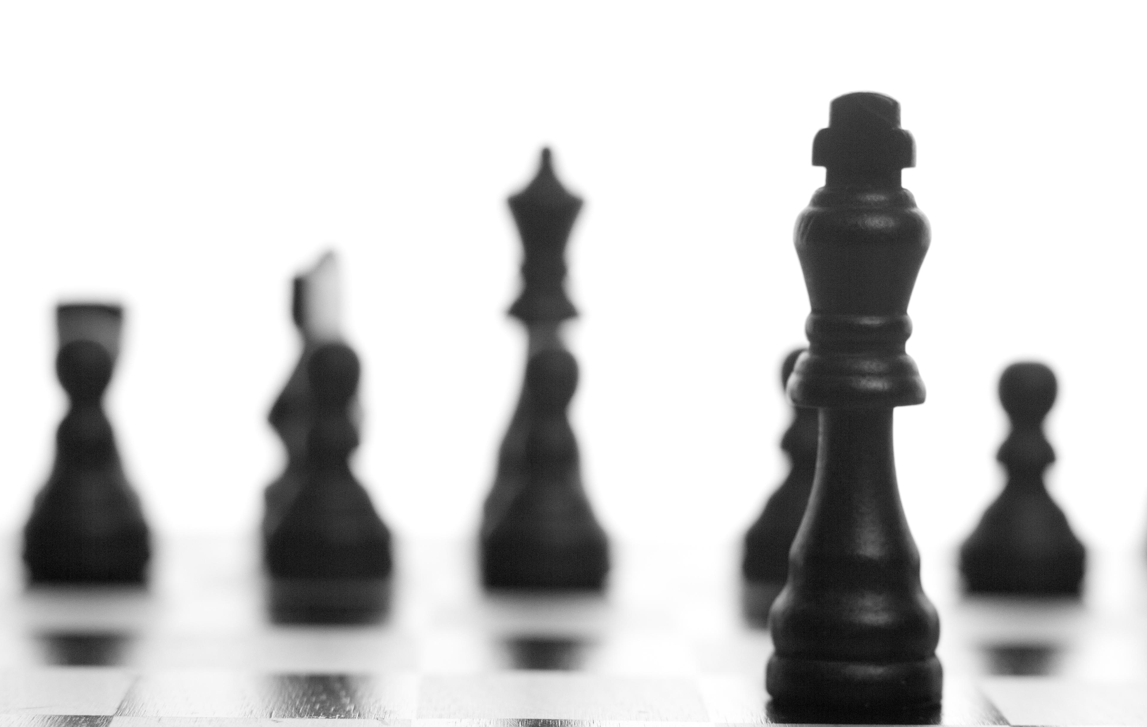 Several black chess pieces are positioned side by side, standing upright.