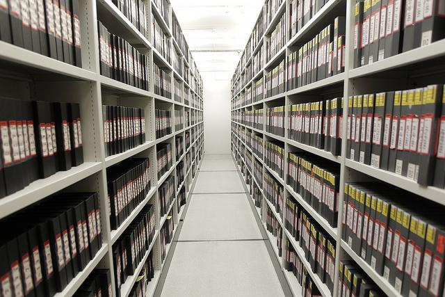 Image of an aisle in a storage hacility with binders/boxes of numbered material.