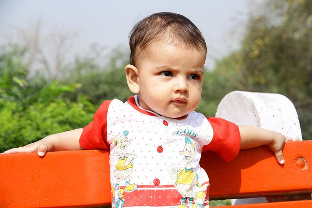 A male baby rests his arms on the top of an outdoor bench and looks into the distance.