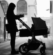 Black and white image of woman's silhouette looking at her phone while pushing baby carriage in a European city