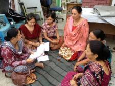 Six women (members of Women's Rehabilitation Center in Nepal) are gathered in a circle, intently listening and discussing.