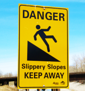 "Yellow warning sign stating, ""Danger Slipper Slope--keep away."" A figure is featured slipping from an incline."