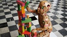 A wooden-like figure of a child builds a colorful tower of blocks. The child sits in a background surrounded by white and black checkered flooring.