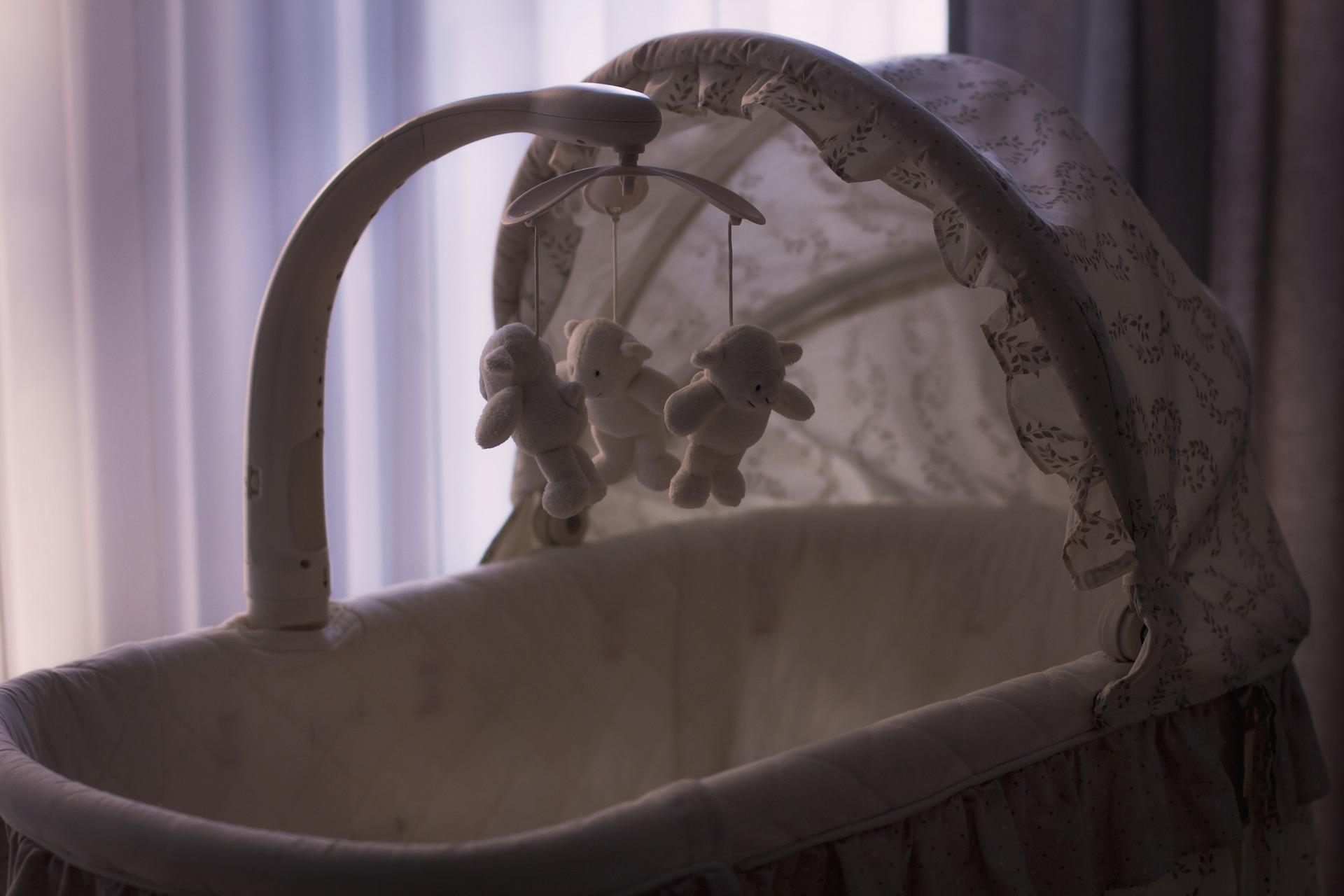 An empty baby cradle, with a spinning mobile of bear toys hanging above.